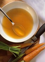 Clear Chicken Broth in Bowl with Spoon and fresh Carrots