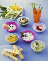 Six different dips; strips of cheese and raw vegetables