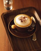 Cappuccino in brown cup and saucer with amarettini