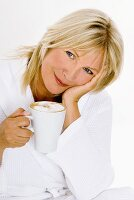 Blond woman holding a cup of cappuccino in her hand