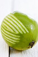 A lime with strips of zest removed