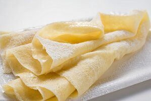 Wafer-thin crêpes with icing sugar on paper plate