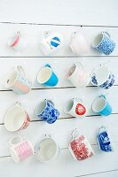 Various mugs and cups hanging on a wooden wall