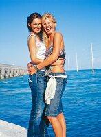 Frauen Kopf an Kopf, stehen dicht beieinander am Meer, lachen