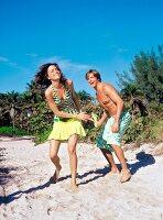 Braungebranntes Paar verspielt am Strand