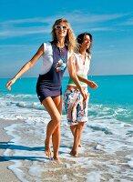 Frauen laufen barfuß im Wasser haben Spaß beim Spaziergang