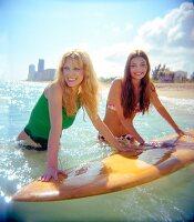 Zwei Frauen im Meer mit gelbem Surfbrett