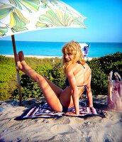 Blonde Frau unter Sonnenschirm in blauem Bikini