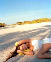 Frau liegt im Schatten im Sand, weißer Badeanzug und Shorts