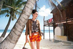 Frau steht an Palme gelehnt, Strand, Hand in der Tasche, Safari-Look