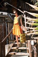 Frau, lächelt, geht Holztreppe runter, Sonnenbrille, Kleid, orange