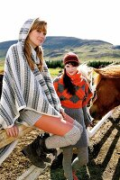 Two beautiful women wearing knitted poncho, hood and cap standing near the fence