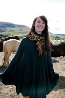 Happy brunette woman wearing poncho and scarf standing in pasture and laughing