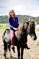 Pretty blonde woman in blue sweater riding a black icelandic horse, looking over shoulder