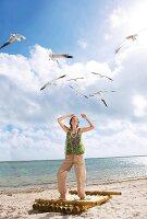 Frau steht auf Floß am Strand, blick t in Himmel, lacht, Möwen