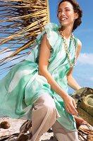 Frau, brünett, Chiffonkleid grün mit Rüschenärmel, Blick seitlich, lacht