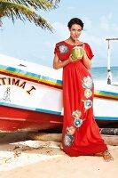 Strandmode: Frau im Seidenkleid in Rot am Strand trinkt aus Kokosnuss