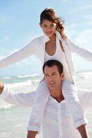 Tochter bei Vater auf den Schultern, Strand, sommerlich, glücklich