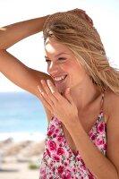 Frau in geblümtem Sommerkleid und Strohhut, lachend
