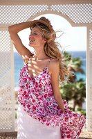 Frau in geblümtem Sommerkleid, Strohhut in einem Strandpavillon