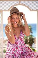 Frau im Sommerkleid hält mit beiden Händen ihren Strohhut fest
