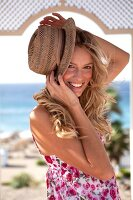 Frau im Sommerkleid hält, hält ihren Strohhut schräg am Kopf