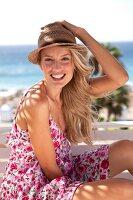 Frau im Sommerkleid mit Strohhut lächelt in die Kamera