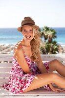 Frau im geblümten Sommerkleid mit Strohhut sitzt auf einer Bank