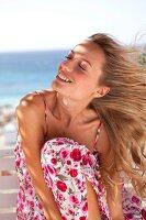 Frau im geblümten Sommerkleid hält lächelnd das Gesicht in den Wind