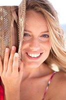 blonde Frau hält, hält ihren Strohhut schräg am Gesicht