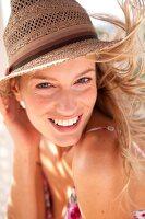 Frau mit Strohhut, zerzaustes Haar, lächelt in die Kamera