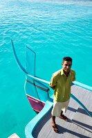 Malediver steht auf Boot, Insel Velighanduhuraa, Malediven