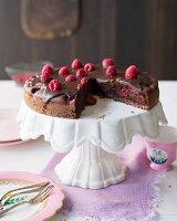 Crunchy chocolate cake with raspberries, sliced