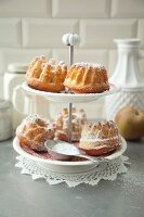 Mini apple and almond Bundt cakes with icing sugar on a cake stand