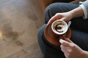 Woman holding cappuccino with euro motif