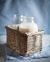 Two bottles of milk in a basket