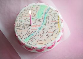 A small wedding cake topped with a city map and a symbolic candle