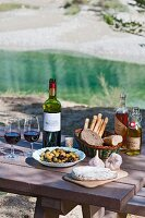 Wine and food on a wooden table by a river (Canyon du Verdon, France)