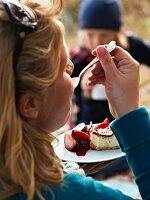 A woman enjoying a cheesecake with plum compote