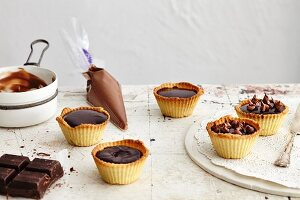 Tartlets with chocolate, nougat and caramel being made