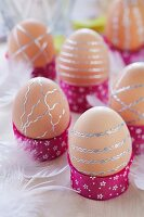 Brown eggs decorated with strips of silver stickers in hand-crafted egg cups