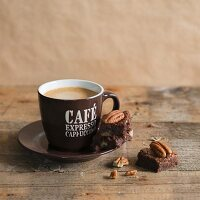 A chocolate and pecan nut brownie next to an espresso cup