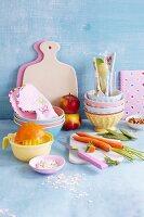 An arrangement of children's tableware, fruit and vegetables