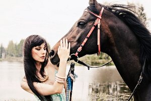 A young, dark-haired woman wearing a spaghetti strap top stroking a horse