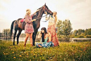 Three young women wearing hippie-style clothing with a horse by a lake