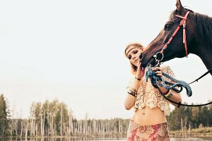 A young blonde woman wearing hippie-style clothing stroking a horse by a lake