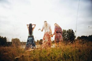 Three young women by a lake wearing hippie-style clothes