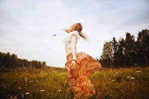 A young blonde woman wearing hippie-style clothing dancing over a meadow