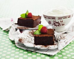 Two slices of chocolate cake with raspberries served with whipped cream
