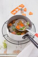 Soup with sausage dumplings and carrot hearts